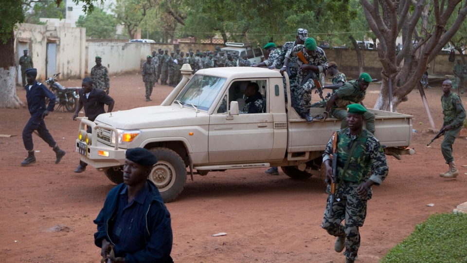 Malian soldiers loyal to coup leader Capt. Amadou Haya Sanogo secure the location as he arrives at his headquarters at Kati military base, just outside Bamako, Tuesday, March 27, 2012. (AP / Rebecca Blackwell)