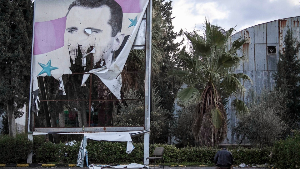 A Free Syrian Army fighter offers evening prayers beside a damaged poster of Syria's President Bashar Assad during heavy clashes with government forces in Aleppo, Syria, Saturday, Dec. 8, 2012. (AP / Narciso Contreras)