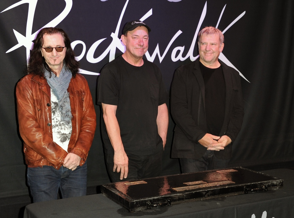 Members of Rush, from left, Geddy Lee, Neil Peart, and Alex Lifeson, at the RockWalk induction of Rush at Guitar Center in Los Angeles, on Nov. 20, 2012. (Invision / Richard Shotwell/)