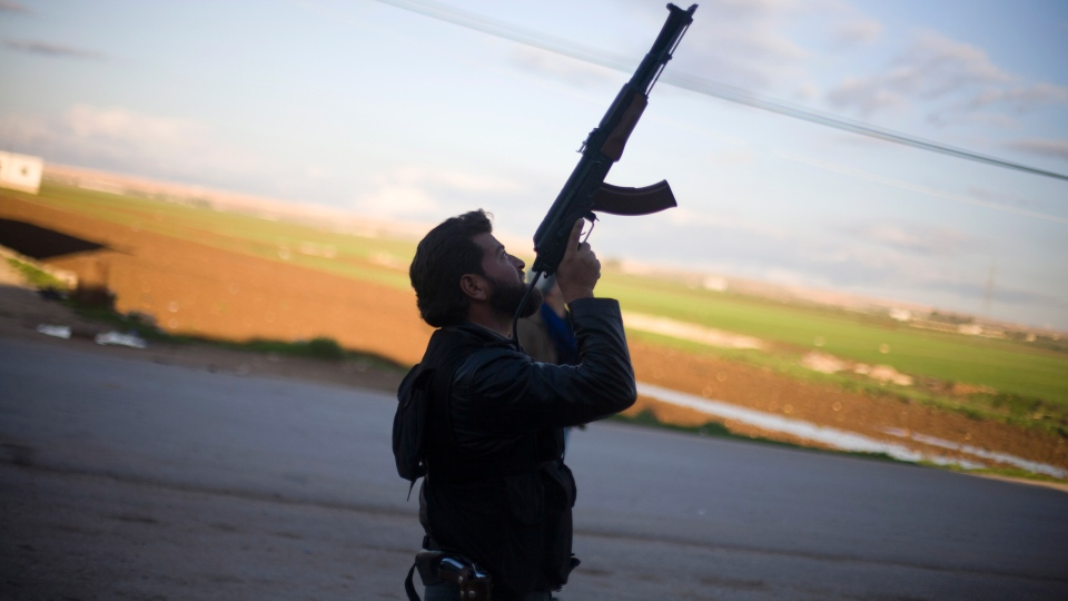 A Free Syrian Army fighter points his weapon as he watches a Syrian Army jet, not pictured, in Fafeen village, north of Aleppo province, Syria, Tuesday, Dec. 11, 2012. (AP / Manu Brabo)