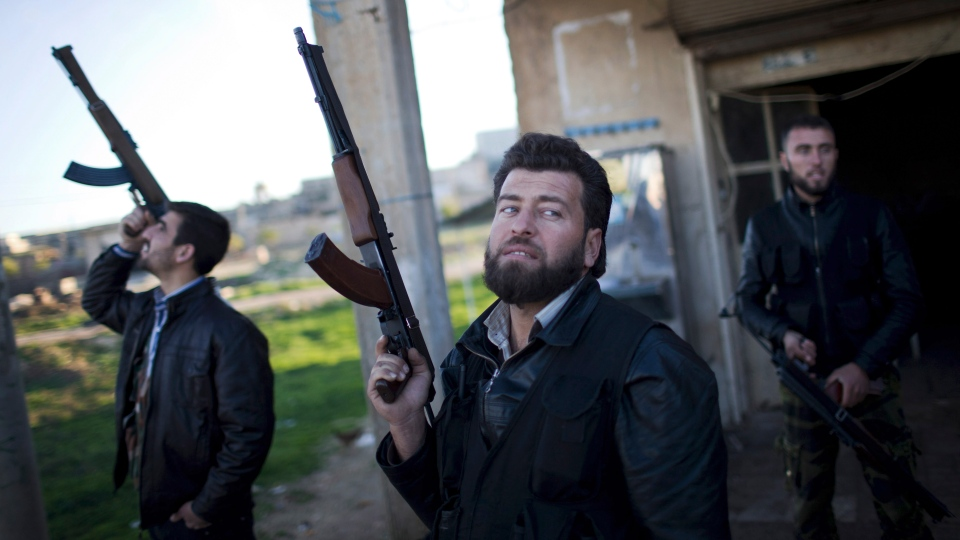 Free Syrian Army fighters look at a Syrian Army jet, not pictured, in Fafeen village, north of Aleppo province, Syria, Tuesday, Dec. 11, 2012. (AP / Manu Brabo)