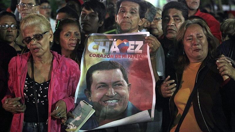 People, one holding an image of Venezuela's President Hugo Chavez, gather to pray for him at Simon Bolivar square in Caracas, Venezuela, Tuesday, Dec. 11, 2012. (AP / Fernando Llano)