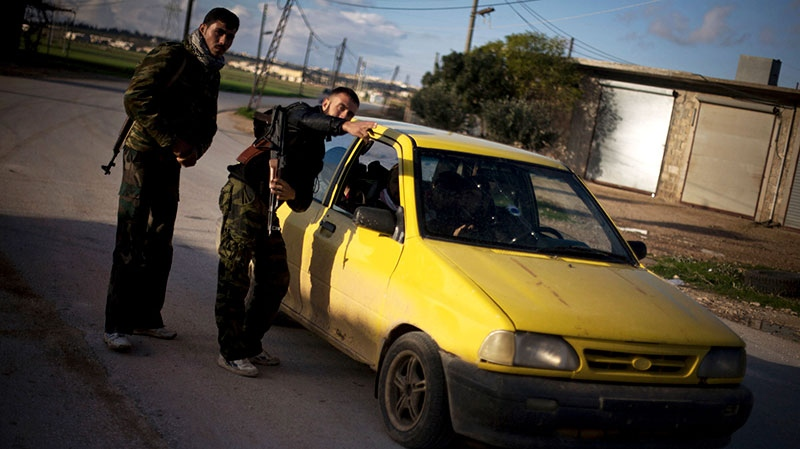 Free Syrian Army fighters stop a car at a check point at the entrance of Fafeen village, north of Aleppo province, Syria, Tuesday, Dec. 11, 2012. (AP / Manu Brabo)
