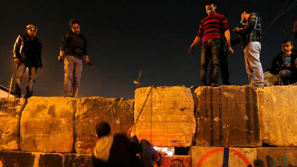 Protesters dismantle a wall guarding the presidential palace during a demonstration in Cairo, Egypt, Tuesday, Dec. 11, 2012. (AP / Petr David Josek)