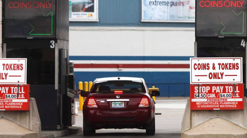 A driver pays toll before getting on the Ambassador Bridge at the Windsor-Detroit inetrnational crossing on 'Black Friday' from Windsor, Ontario, Friday November, 26, 2010. (Brent Foster / THE CANADIAN PRESS)