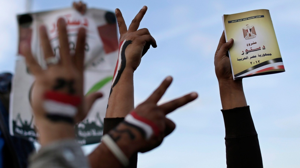 Supporters of President Mohammed Morsi with the Egyptian national flag painted on their hands, flash victory signs as one holds a copy of Egypt's draft constitution, right, during a demonstration, in Cairo, Egypt, Tuesday, Dec. 11, 2012. (AP / Hassan Ammar)