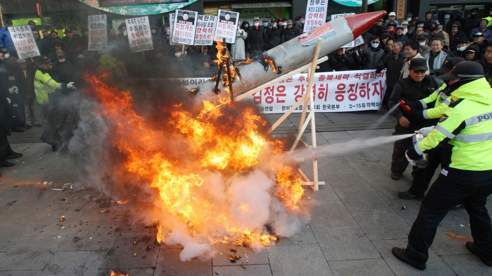 South Korean protesters burn a mock rocket as police officers spray fire extinguishers during a rally denouncing North Korea's rocket launch in Seoul, South Korea, Wednesday, Dec. 12, 2012. (AP / Ahn Young-joon)