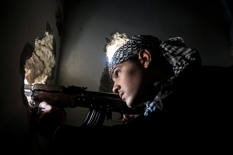 A Free Syrian Army fighter aims his weapon during heavy clashes with government forces in Aleppo, Syria on Dec. 10, 2012. (AP Photo/Narciso Contreras)