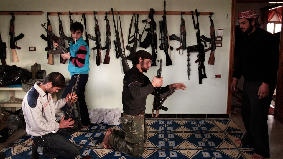 Syrian rebels clean their weapons at their headquarters in Maaret Misreen, near Idlib, Syria, Wednesday, Dec. 12, 2012. (AP / Muhammed Muheisen)