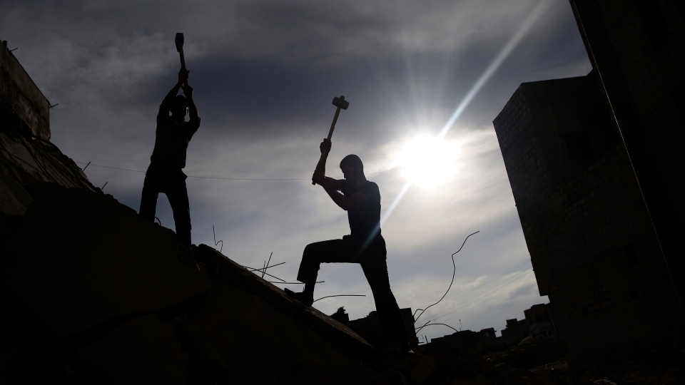 Syrian men use sledgehammers to break the concrete of a residential building destroyed in a government airstrike, while searching for belongings under the rubble, in Maaret Misreen on Dec. 12, 2012. (AP Photo/Muhammed Muheisen)