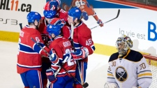 Montreal Canadiens' Brian Gionta (21) is congratulated by teammates Andrei Kostitsyn, (46) Jaroslav Spacek (6) and Roman Hamrlik (top) after scoring against Buffalo Sabres goaltender Ryan Miller, right, during second period NHL hockey action in Montreal, Saturday, Nov. 27, 2010. (AP Photo/The Canadian Press, Graham Hughes)