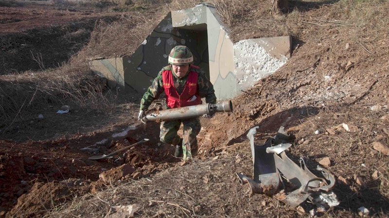 A member of a South Korean military explosives team removes a North Korean ordinance Sunday, Nov. 28, 2010, from where it struck in front of a bunker on South Korea's Yeonpyeong Island. (AP / David Guttenfelder)
