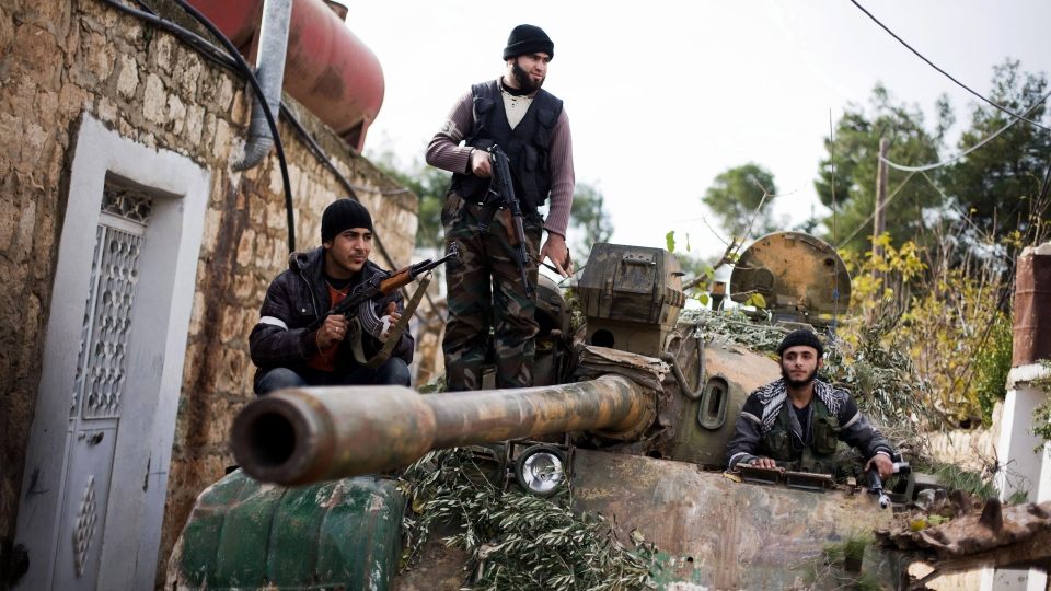 Kurdish members of the FSA are seen on a tank stolen from the Syrian Army in Fafeen village, north of Aleppo province, Syria, Wednesday, Dec. 12, 2012 (AP / Manu Brabo)