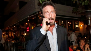 Anti-virus software founder John McAfee talks on his mobile phone as he walks on Ocean Drive in the South Beach area of Miami Beach, Fla., on his way to dinner Wednesday, Dec 12, 2012. (AP / Alan Diaz)