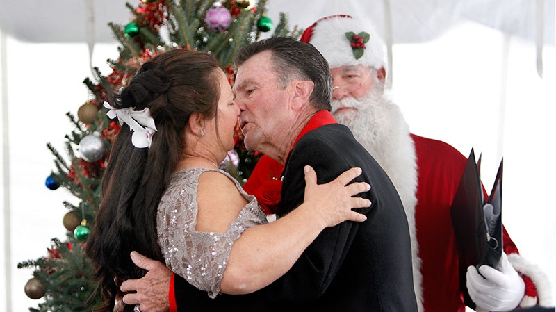 Dorinda Patterson, 55, left, and Richard Eaton, 66, kiss after becoming husband and wife in a ceremony officiated by Capt. Glenn Rosenberger, dressed as Santa Claus, in Royal Palm Beach, Fla., Wednesday afternoon, Dec. 12, 2012. (The Palm Beach Post, Bill Ingram)