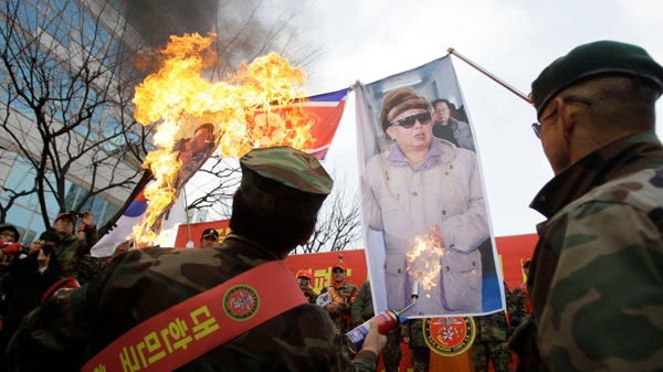 Former South Korean marines burn images of North Korean leader Kim Jong Il, right, and his son Kim Jong Un, during a rally denouncing North Korea in Seoul, South Korea, Saturday, Nov. 27, 2010. (AP / Wally Santana)