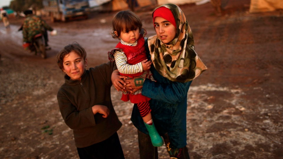 Syrian sisters, Asma Abdullah, 8, left, Sumayya, 1, and Naima, 10, who fled their home with their family in Idlib due to government airstrikes, stand at a camp for displaced Syrians in the village of Atmeh, Syria, Thursday, Dec. 13, 2012. (AP / Muhammed Muheisen)