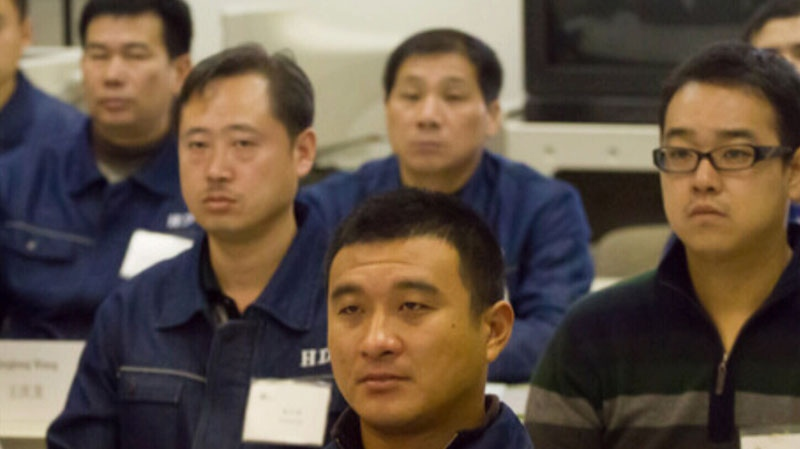 Chinese HD Mining employee Huizhi Li, pictured at the far right, has filed a human rights complaint arguing that leaflets distributed by the United Steelworkers Union are likely to create contempt for workers flown in from China to work in B.C.