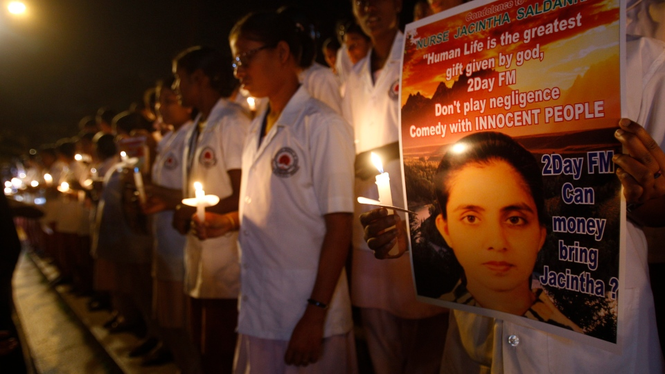 Students of a nursing college, one of them holding a poster depicting nurse Jacintha Saldanha, participate in a candle-lit vigil organized by a local politician in Bangalore, India, Thursday, Dec. 13, 2012. (AP / Aijaz Rahi)