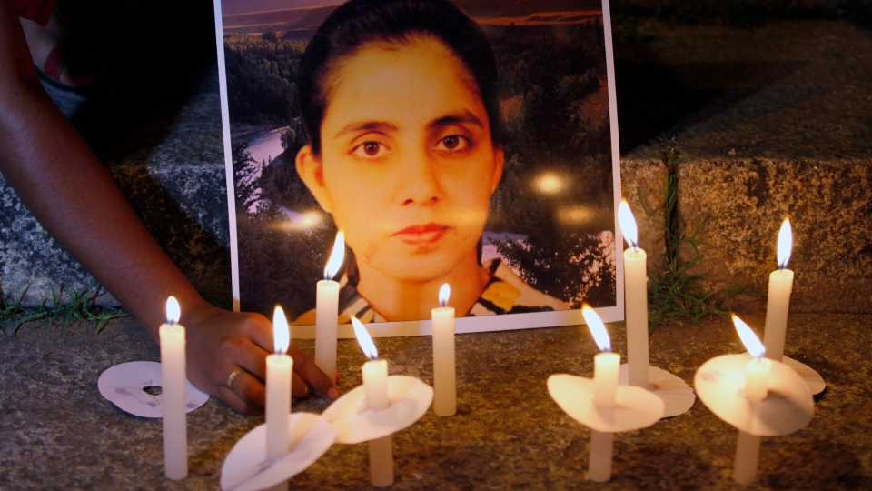 A student of a nursing college places a candle in front of a picture depicting nurse Jacintha Saldanha, during a candle-lit vigil organized by a local politician in Bangalore, India, Thursday, Dec. 13, 2012. (AP / Aijaz Rahi)