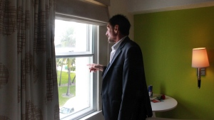 John McAfee looks out the window in his room at the Beacon Hotel on South Beach in Miami, on Thursday, Dec. 13, 2012. (El Nuevo Herald, CM Guerrero)