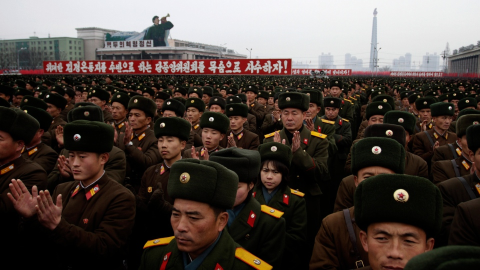 North Korean soldiers applaud near slogans honouring their leadership during a mass rally organized to celebrate the success of a rocket launch that sent a satellite into space on Kim Il Sung Square in Pyongyang, North Korea, Friday, Dec. 14, 2012. (AP / Jon Chol Jin)