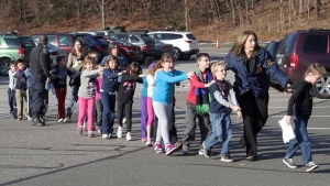 Connecticut State Police lead children from the Sandy Hook Elementary School in Newtown, Conn., following a reported shooting on Friday, Dec. 14, 2012. (AP Photo/Newtown Bee/Shannon Hicks)