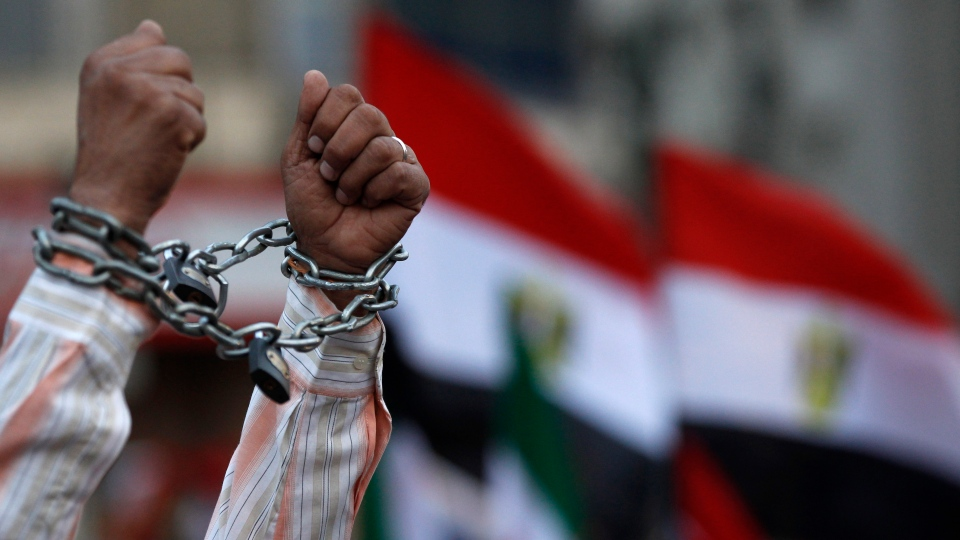 A protester shows his chained hands during a demonstration against a constitution drafted by Islamist supporters of President Mohammed Morsi in Tahrir square in Cairo on Dec. 14, 2012. (AP Photo/Petr David Josek)
