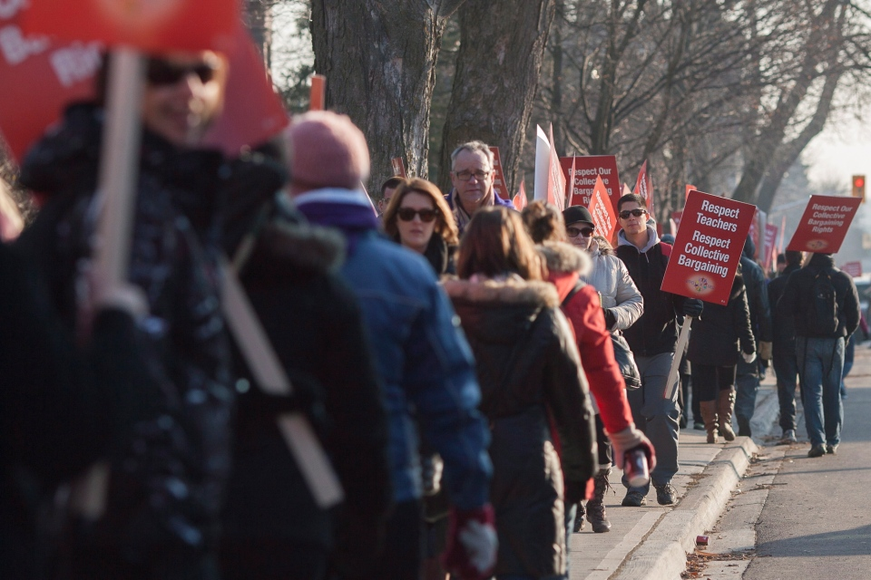 Teachers carry picket signs outside the constituency office of MPP Liz Sandals in Guelph, Ont., on Friday, Dec. 14, 2012. (Adam Dietrich / THE CANADIAN PRESS)