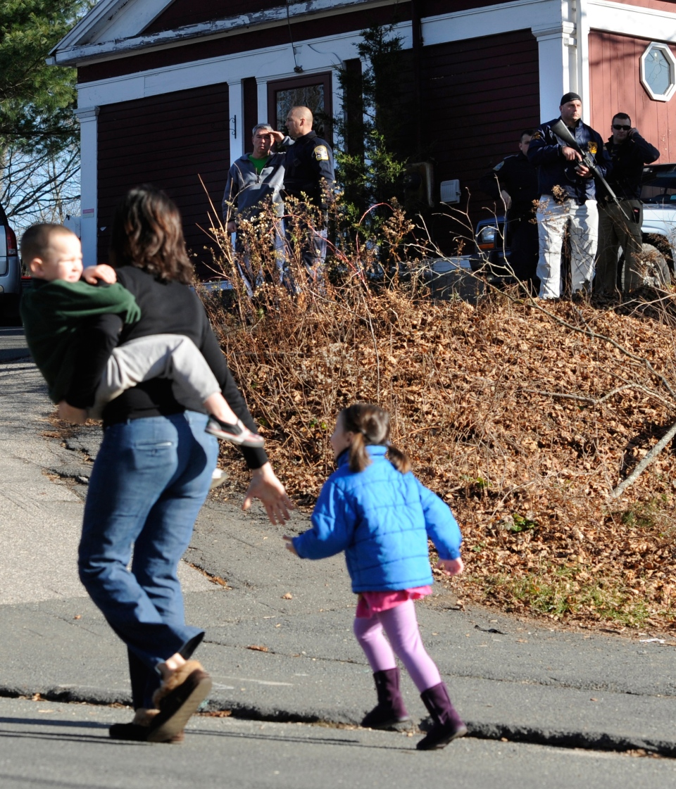 A mother runs with her children as police above canvass homes in the area following a shooting at the Sandy Hook Elementary School in Newtown, Conn., about 96 km northeast of New York City, Friday, Dec. 14, 2012. (AP / Jessica Hill)