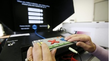 An Elections Canada official demonstrates an assistive voting device at an advance voting polling station in Winnipeg Tuesday, Nov. 23, 2010. (John Woods / THE CANADIAN PRESS)