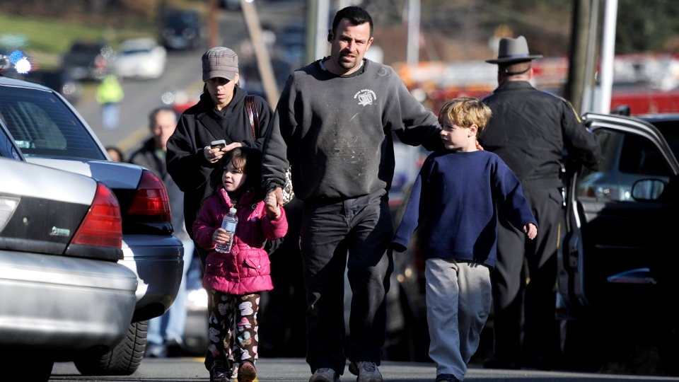 Parents leave a staging area after being reunited with their children following a shooting at the Sandy Hook Elementary School in Newtown, Conn., about 60 miles (96 kilometers) northeast of New York City, Friday, Dec. 14, 2012. (AP /Jessica Hill)