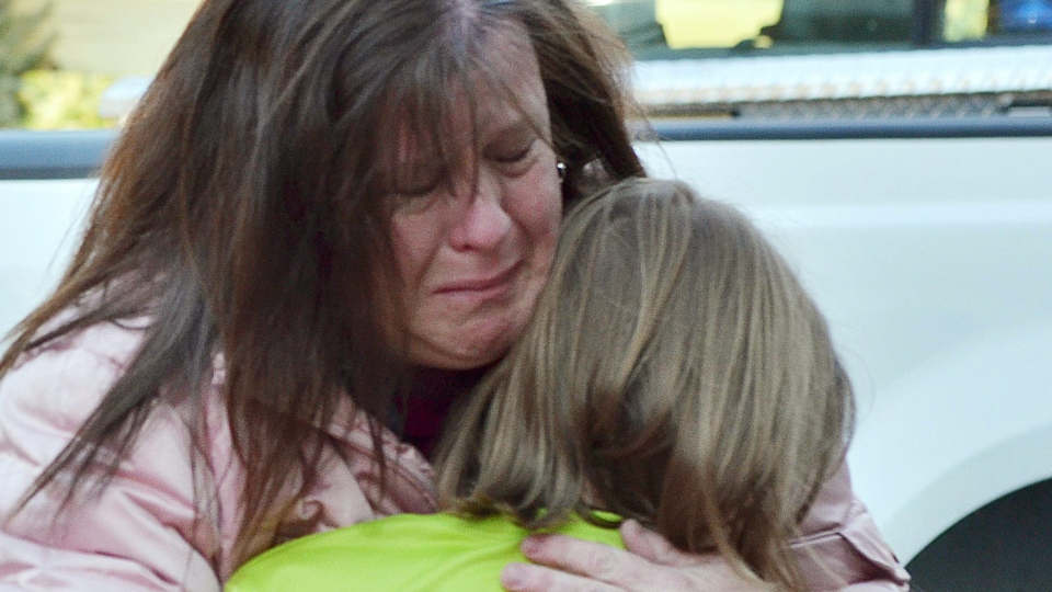 A mother hugs her daughter following a shooting at the Sandy Hook Elementary School in Newtown, Conn., Friday, Dec. 14, 2012. (The New Haven Register, Melanie Stengel)