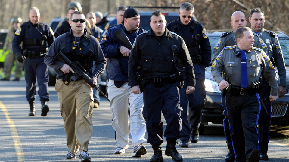 Law enforcement officers canvass the area following a shooting at the Sandy Hook Elementary School in Newtown, Conn., about 96 kilometres northeast of New York City, Friday, Dec. 14, 2012. (AP / Jessica Hill)