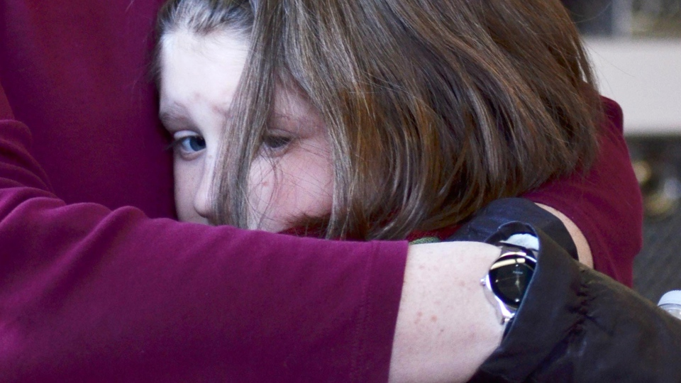 A mother hugs her daughter following a shooting at the Sandy Hook Elementary School in Newtown, Conn., 96 km northeast of New York City, Friday, Dec. 14, 2012. (The New Haven Register / Melanie Stengel)