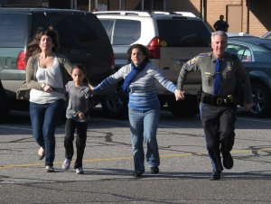 In this photo provided by the Newtown Bee, a police officer leads two women and a child from Sandy Hook Elementary School in Newtown, Conn., Friday, Dec. 14, 2012.