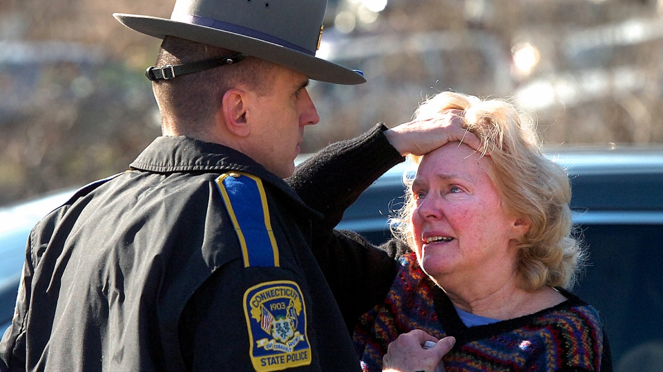 A woman speaks with a Connecticut State Police officer near Sandy Hook Elementary School in Newtown, Conn., Friday, Dec. 14, 2012 (AP / The Hour, Alex von Kleydorff)