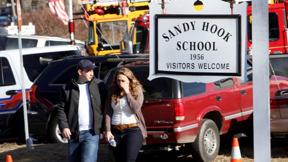 Parents walk away from the Sandy Hook Elementary School with their children following a shooting at the school in Newtown, Conn.  Friday, Dec. 14, 2012.  (AP / The Journal News, Frank Becerra Jr.)