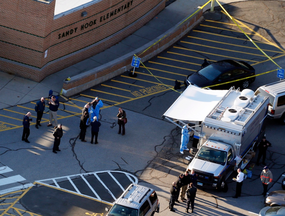 Officials are on the scene outside of Sandy Hook Elementary School in Newtown, Conn., on Friday, Dec. 14, 2012. (AP/Julio Cortez)