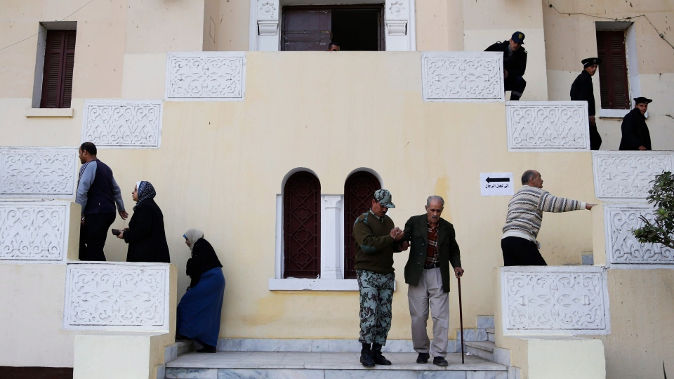 An Egyptian soldier helps an elderly man after casting his vote during a referendum on a disputed constitution drafted by Islamist supporters of President Mohammed Morsi in Cairo, Egypt, Saturday, Dec. 15, 2012. (AP / Petr David Josek)