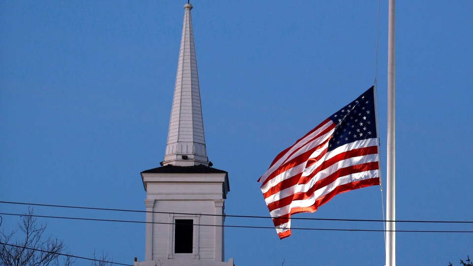 An American flag flies at half-staff as dawn breaks, Saturday, Dec. 15, 2012 in Newtown, Conn. (AP / Jason DeCrow)