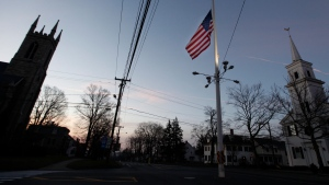 An American flag flies at half-staff as dawn breaks, in Newtown, Conn., Saturday, Dec. 15, 2012. (AP / Jason DeCrow)