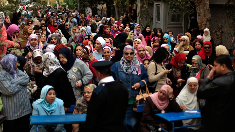 Egyptian women line up outside a polling station to cast their votes during a referendum on a disputed constitution drafted by Islamist supporters of President Morsi in Cairo, Egypt, Saturday, Dec. 15, 2012.(AP / Khalil Hamra)