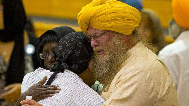 Mourners console one another at the funeral and memorial service for the six victims of the Sikh temple of Wisconsin mass shooting in Oak Creek, Wis., Friday, Aug 10, 2012. (AP / Jeffrey Phelps)