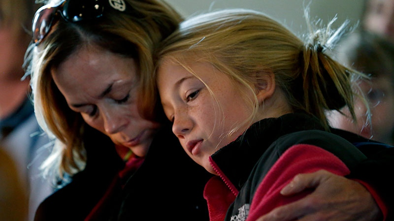 Molly Delaney, left, holds her 11-year-old daughter, Milly Delaney, during a service in honor of the victims who died a day earlier when a gunman opened fire at Sandy Hook Elementary School in Newtown, Conn., as people gathered at St. John's Episcopal Church in the Sandy Hook village of Newtown, Conn., Saturday, Dec. 15, 2012. (AP / Julio Cortez)