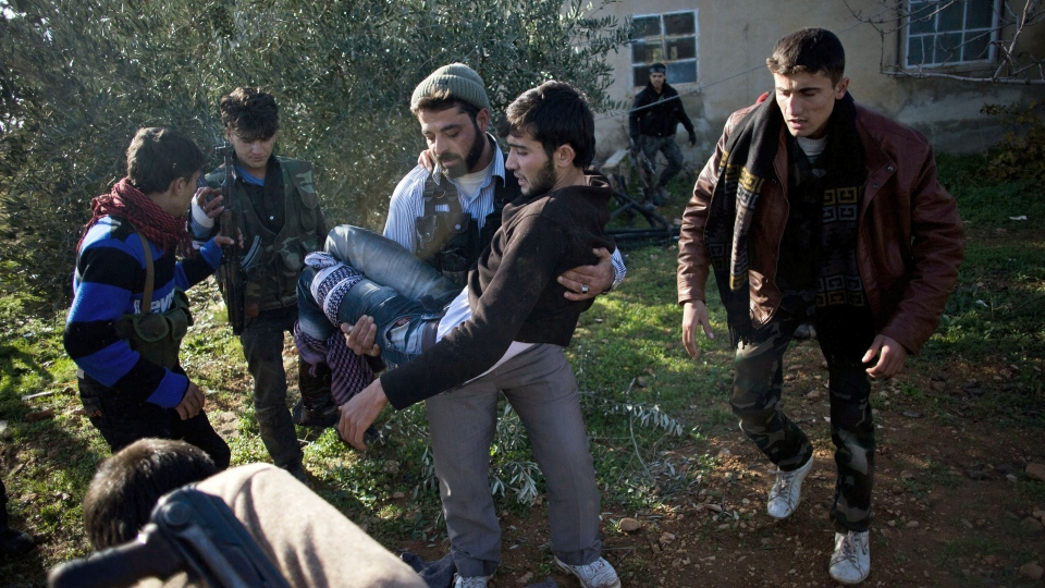 Free Syrian Army fighter carries an injured comrade during the assault on a military base in Tal Sheen, Syria, Saturday, Dec 15, 2012 (AP / Manu Brabo)