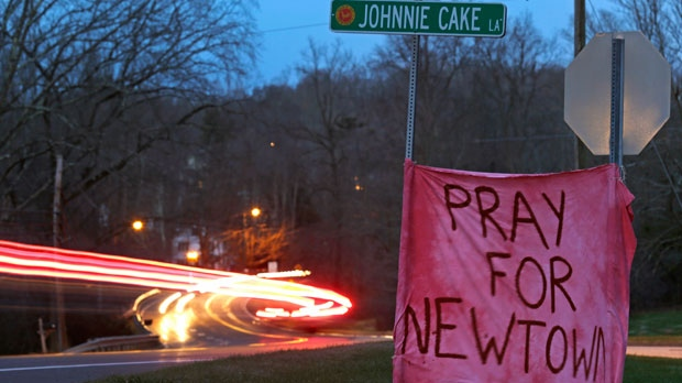 Tail lights streak past a sign asking for prayer on Main Street heading into the village of Newtown, Conn., at dusk on Saturday, Dec. 15, 2012. (AP Photo/Charles Krupa)