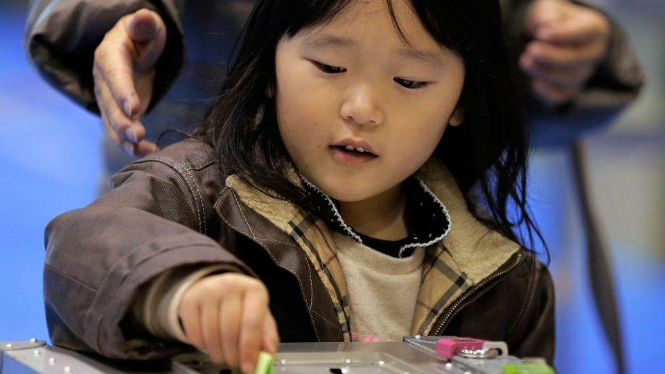 A girl places her mother's vote into a ballot box at a polling station in Tokyo, Sunday, Dec. 16, 2012. (AP / Itsuo Inouye)