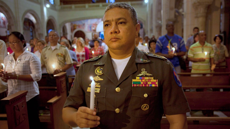 A member of Venezuela's army holds a candle during a mass in support of Venezuela's President Hugo Chavez in Havana, Cuba, Thursday, Dec. 13, 2012. (AP / Ramon Espinosa)