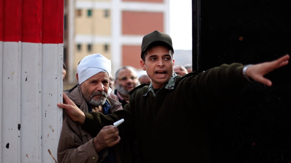 An Egyptian solider speaks to a man outside a polling station during a referendum on a disputed constitution drafted by Islamist supporters of President Mohammed Morsi in Cairo, Egypt, Saturday, Dec. 15, 2012. (AP / Khalil Hamra)